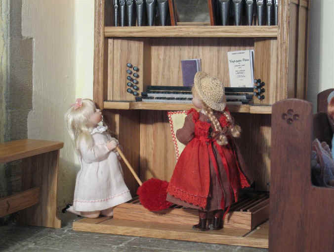 Adele and Priscilla Jane clean the two manual pipe organ in the church.
